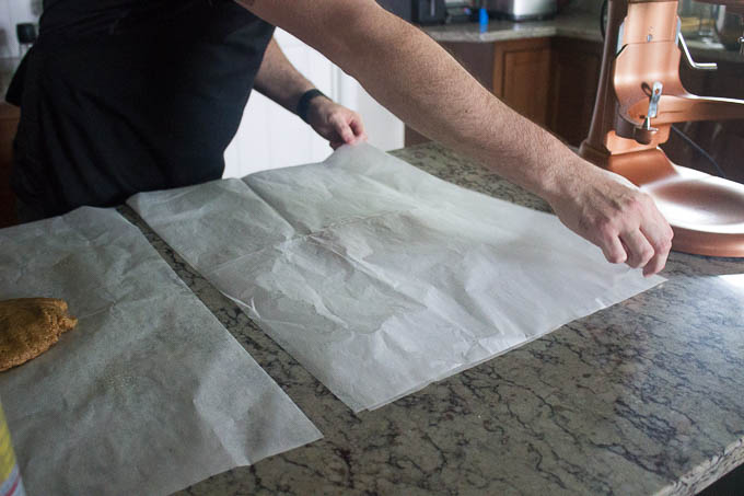 "Working with one piece of dough at a time, roll it between two pieces of lightly greased parchment until it's 1/16"" thick. Try to keep the dough a uniform thinness throughout."