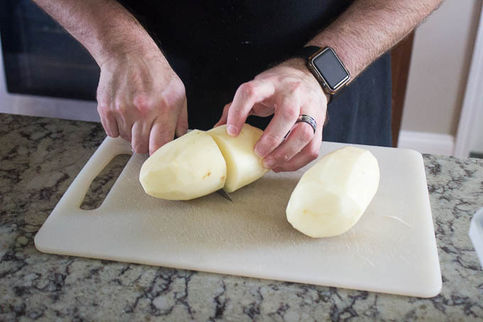 Peel your potatoes. Cut them in half.