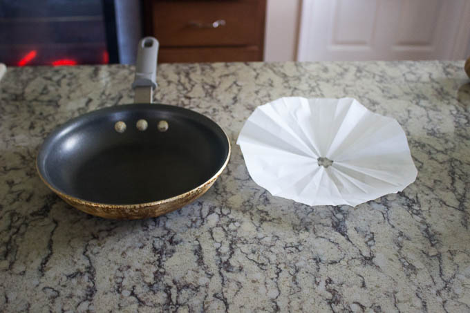 Take a piece of parchment paper, fold it in quarters, then fold it like a paper air plane. Measure from the center of the pan out. Cut the tip off, and the extra. set aside for later.