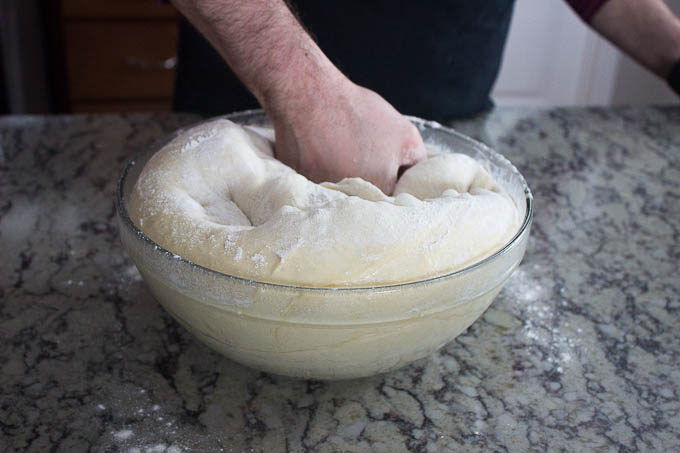 Unwrap your dough and sprinkle flour over the top. Punch down and turn out onto a floured surface.
