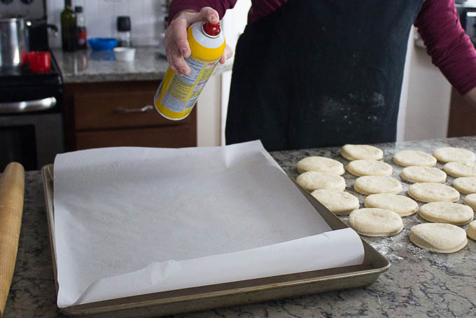 Roll your dough out to about a half inch thick. Using your cutter, mark your dough for maximum usage. Cut, and transfer to a sheet tray with greased parchment paper.