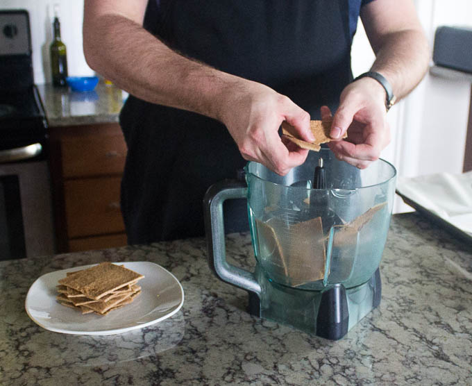 Break your graham crackers into smaller pieces into the bowl of a food processor and pulse until you've got a fine and fairly even consistency. I say fairly because there will be some pieces that are a bit larger. That's a good thing as it gives it a more interesting texture.