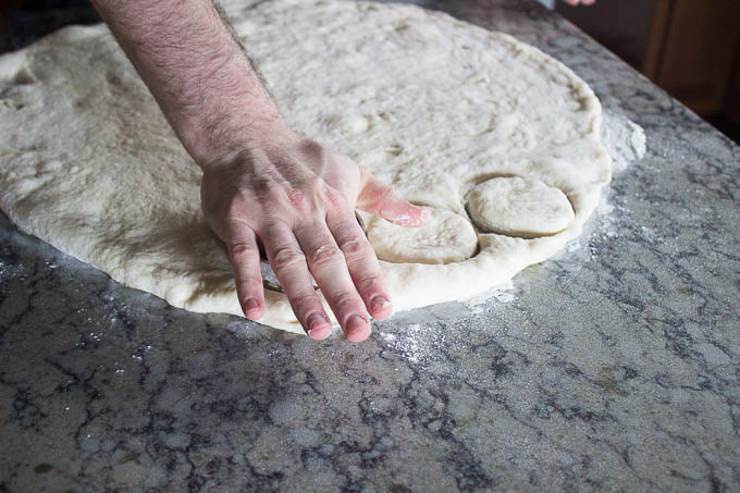 "Line a sheet tray with parchment paper and spray with non-stick spray. Turn your dough out onto a floured work surface and roll out about 1/2"" thick. Using a large round cutter, cut out your doughnuts and set them on your prepared parchment. Cover and allow to rise about 30 minutes."