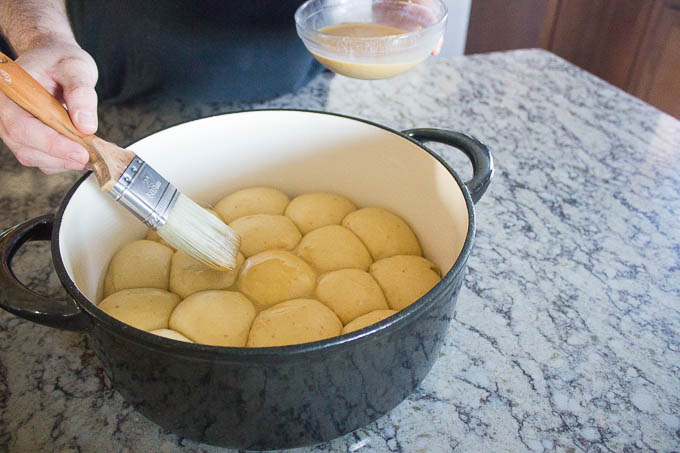 Once your rolls have doubled in size, GENTLY brush your egg wash over the tops of each rolls.