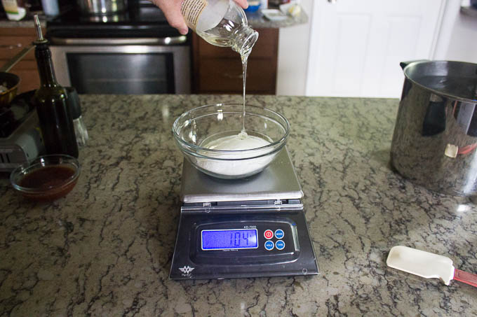 We want to end up with a total of 240 g of fructose and corn syrup, so we are going to weigh out a bit extra to make up for any potential loss. That's why we're using 130g each of sweeteners. Mix the sugars together, Then way out the 240 g of sweeteners into a mason jar.