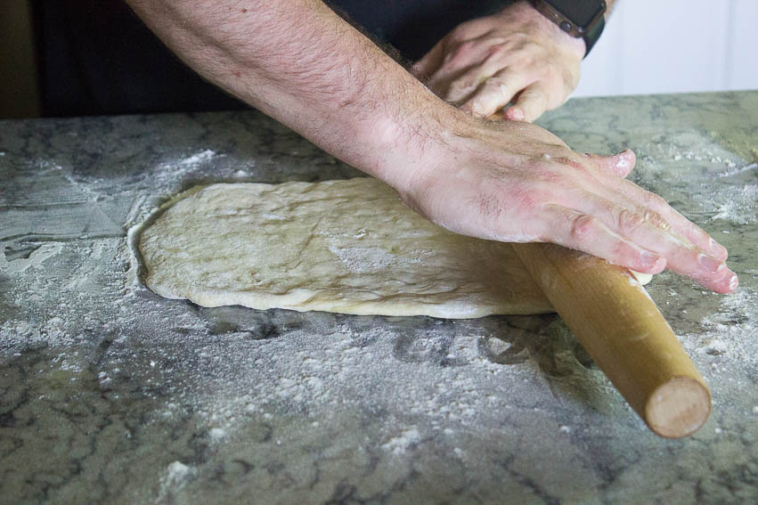 "Once the dough has risen again, turn it out onto the table and either leave it whole or cut it in half for a more personal sized flat bread. Roll the dough out to be about 1/2"" thick. If you're using a pizza stone, you can add your toppings."